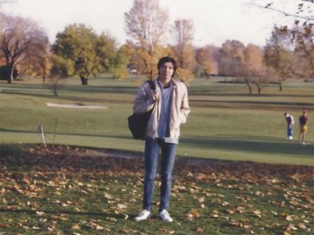 A photo of Xiao as a student holding a backpack and standing near a golf course.