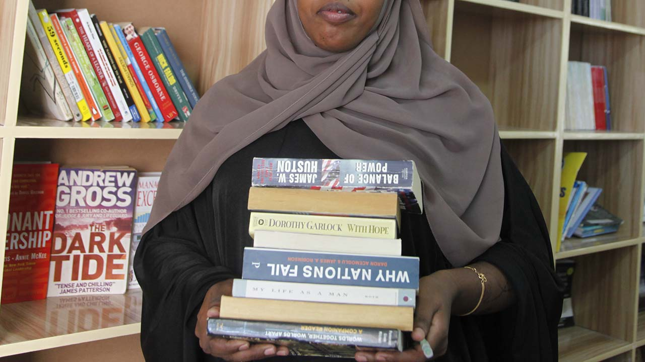 Photo of Somali woman carrying a stack of books in a library