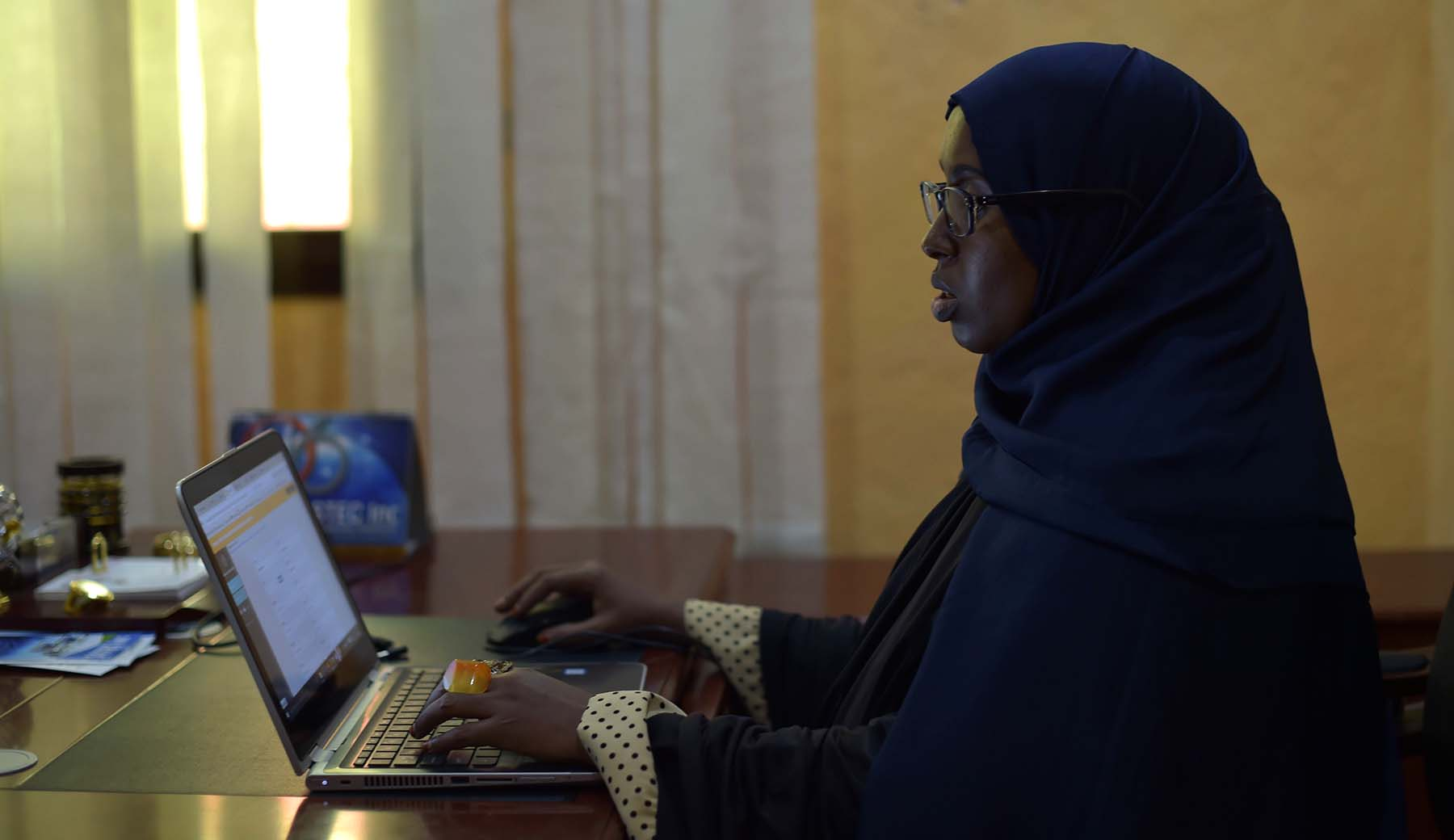 Photo of Sahra Abdikarim Ibrahim using a laptop computer.